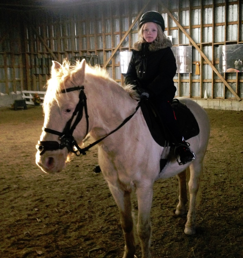 girl poses on horse in riding academy